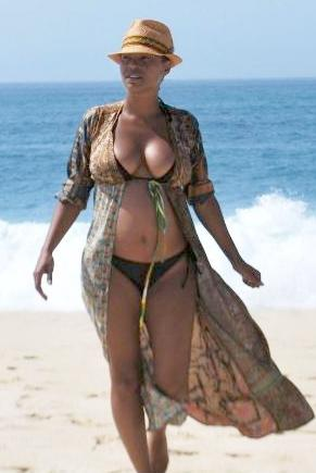 With her voluptuous body and Black hairtype without bra (cup size 34B) on the beach in bikini
