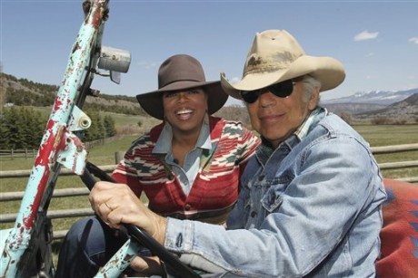 In this file photo taken May 7, 2011 provided by Harpo Productions, Inc., talk-show host Oprah Winfrey rides in a jeep with fashion designer Ralph Lauren at Lauren's RRL Ranch outside Telluride, Colo.