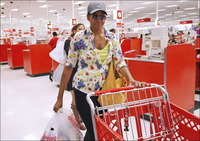 First lady Michelle Obama, wearing a hat and sunglasses, center, stands in line at a Target Department store in Alexandria, Va., Thursday, Sept. 29, 2011, after doing some shopping. (AP Photo/Charles Dharapak)