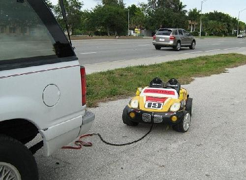 grandparents tow child in toy car