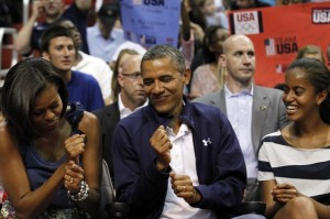 President Barack Obama dances to the music with first lady Michelle Obama, with daughter Malia Obama, right, while attending Team USA and Brazil in an Olympic men's exhibition basketball game, Monday, July 16, 2012, in Washington