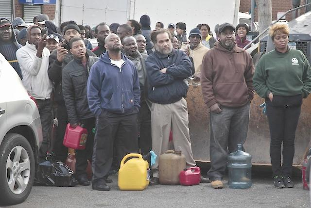 new yorkers waiting at gas station with gas containers