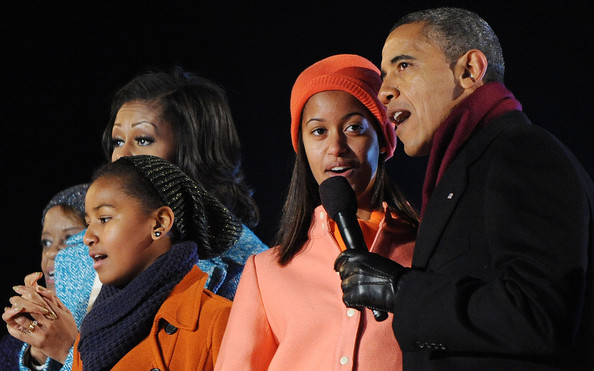 President Barack Obama (R) with his wife first lady Michelle Obama (2nd L) and their daughters Malia (2nd R) and Sasha Obama (C), and mother-in-law Marion Robinson (L) sing during the 90th National Christmas Tree Lighting Ceremony on the Ellipse behind the White House on December 6, 2012 in Washington, DC.
