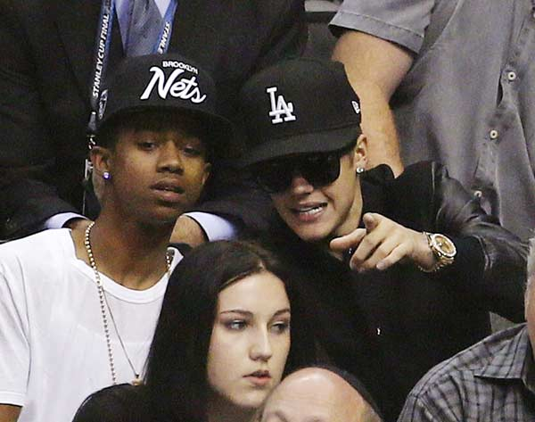 Singer Justin Bieber (R) sits in the crowd as he attends Game 7 of the Western Conference semi-final hockey playoff between the Los Angeles Kings and the San Jose Sharks in Los Angeles, California May 28, 2013
