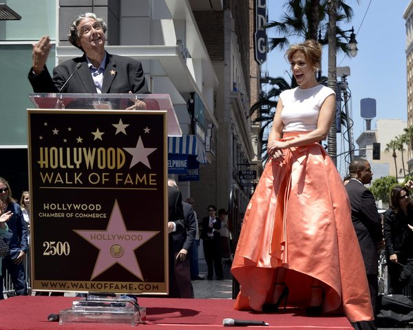 "Jennifer Lopez (R) laughs as filmmaker Gregory Nava (L), who directed her in ""Bordertown,"" speaks during Lopez' star ceremony on the Hollywood Walk of Fame in Hollywood, California (June 20, 2013)"