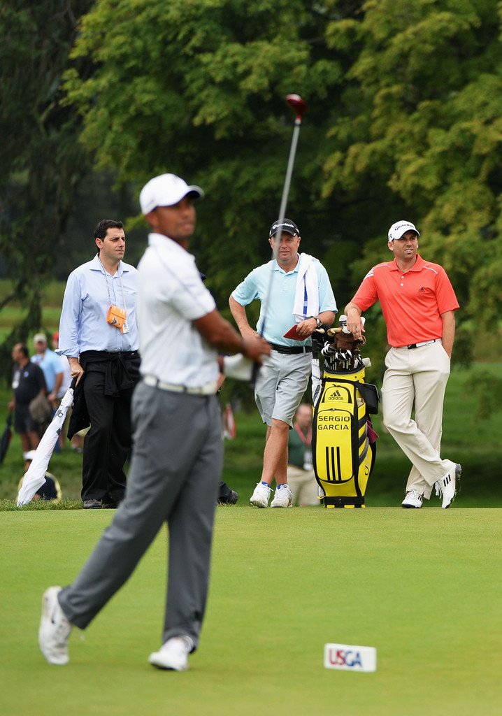 Tiger Woods (L) of the United States hits a shot on the practice range as Sergio Garcia (R) of Spain looks on during a practice round prior to the start of the 113th U.S. Open at at Merion Golf Club on June 10, 2013 in Ardmore, Pennsylvania