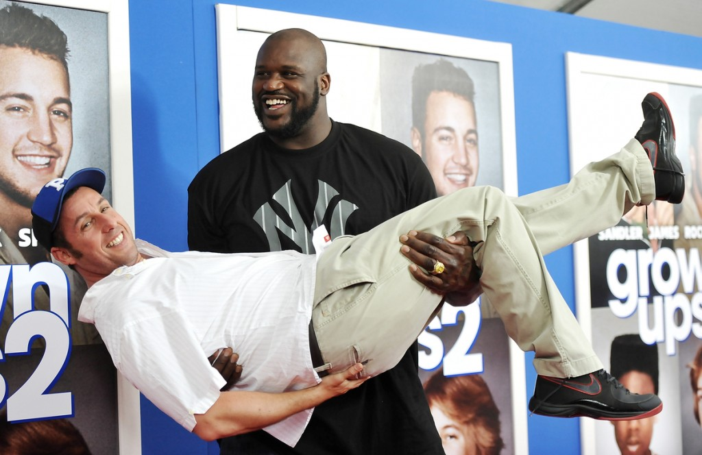 "Former professional basketball player Shaquille O'Neal gives actor Adam Sandler a lift at the premiere of ""Grown Ups 2"" at the AMC Loews Lincoln Square on Wednesday, July 10, 2013 in New York."