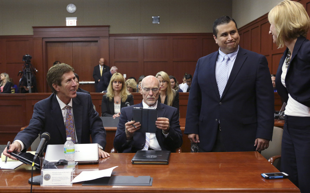 Defendant George Zimmerman (2nd R) smiles while standing with his attorneys Mark O' Mara (L), Don West (2nd L) and Lorna Truett during his murder trial July 12, 2013 in Sanford, Florida