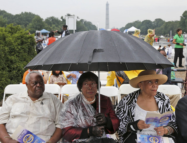 Stanley Samuels and Rita Samuels, from Atlanta, Ga., left, and Sammie Whiting-Ellis, from Washington, D.C., who attended the March on Washington 50 years ago where Martin Luther King, Jr., spoke, wait for the anniversary program to begin in front of the Lincoln Memorial in Washington, Wednesday, Aug. 28, 2013