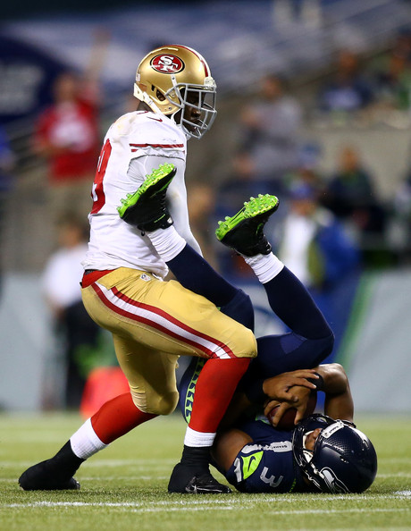 Aldon Smith #99 of the San Francisco 49ers sacks Russell Wilson #3 of the Seattle Seahawks during their game at Qwest Field on September 15, 2013 in Seattle, Washington