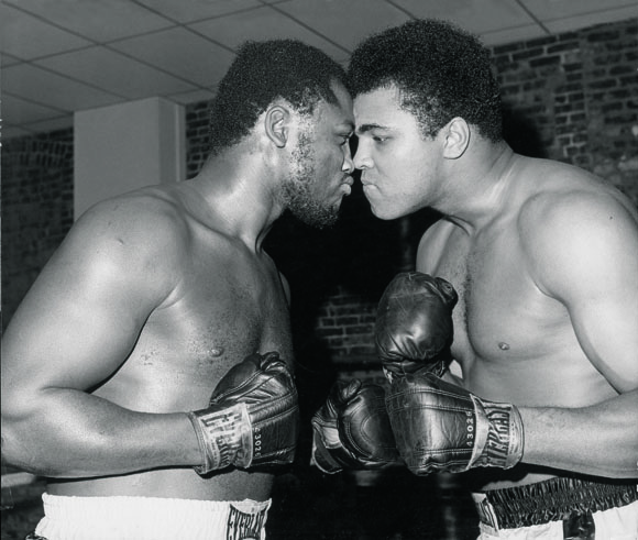 1971 photo of Joe Frazier (L) and Muhammad Ali (R) posing nose to nose leading up to their first of three encounters.