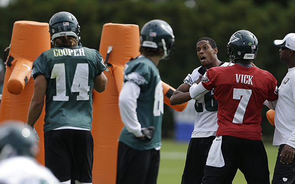 Philadelphia Eagles quarterback Michael Vick, (7) restrain Cary Williams from Riley Cooper (14), during practice at the NFL football team's training facility, Thursday, Sept. 5, 2013, in Philadelphia.