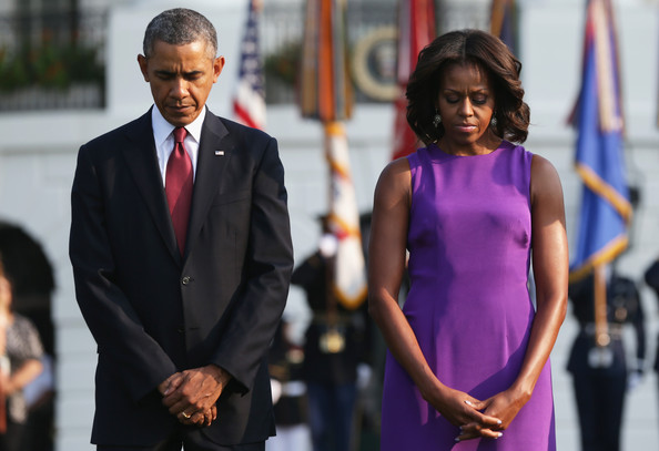 U.S. President Barack Obama and first lady Michelle Obama observe a moment of silence to mark the 12th anniversary of the 9/11 attacks September 11, 2013 at the South Lawn of the White House in Washington, DC.