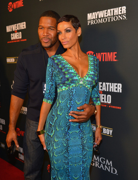 Former NFL player and current talk show host Michael Strahan (L) and TV personality Nicole Murphy arrive at the MGM Grand Garden Arena for the Floyd Mayweather Jr. vs. Canelo Alvarez boxing match on September 14, 2013 in Las Vegas