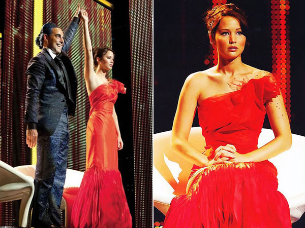 """Caesar Flickerman (Stanley Tucci) holds up the hand of Katniss (Jennifer Lawrence) in her Girl on Fire-themed dress designed by Cinna in """"The Hunger Games"""""""