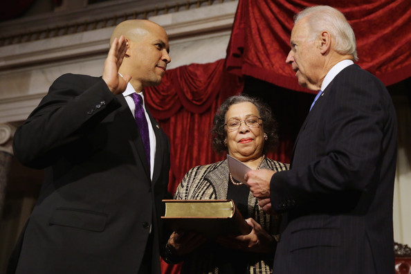 U.S. Vice President Joe Biden (R) administers a ceremonial swearing for Sen. Cory Booker (D-NJ) (L) as his mother Carolyn Booker holds a Bible in the Old Senate Chamber at the U.S. Captiol October 31, 2013 in Washington, DC.