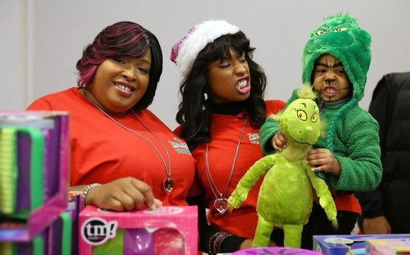 Julia Hudson, left, smiles as Jennifer Hudson and Jennifer's son, David Otunga Jr., make Grinch faces Monday during the Julian D. King Gift Foundation's Christmas toy giveaway at the Ray and Joan Kroc Corps Community Center in Chicago