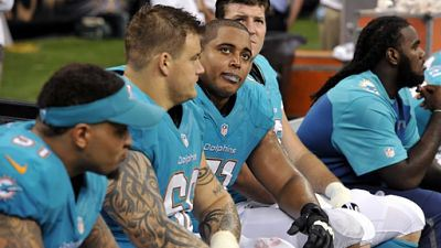 Miami Dolphins guard Richie Incognito (68), second from left,  and tackle Jonathan Martin (71), third from left, sit on the bench in the second half of an NFL football game against the New Orleans Saints in New Orleans. (Sept. 30, 2013)