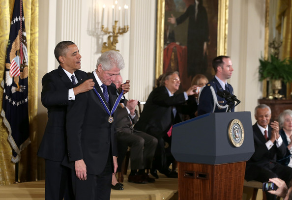 President Barack Obama (L) awards the Presidential Medal of Freedom to former U.S. President Bill Clinton in the East Room at the White House on November 20, 2013 in Washington, DC