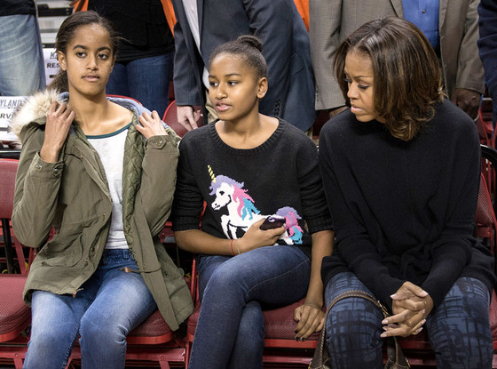 (L-R) Malia, Sasha and Michelle Obama in their seats before a college basketball game between the Oregon State Beavers and the Maryland Terrapins on November 17, 2013 at the Comcast Center in College Park, Maryland