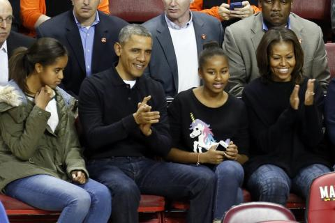President Barack Obama and First Lady Michelle Obama with their daughters Malia (L) and Sasha (R) in their seats before a college basketball game between the Oregon State Beavers and the Maryland Terrapins on November 17, 2013 at the Comcast Center in College Park, Maryland