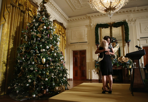 U.S. first lady Michelle Obama (R) hugs Diane Cole of Phoenix, Arizona, at the East Room of the White House during an event to preview the 2013 holiday decorations December 4, 2013 in Washington, DC.