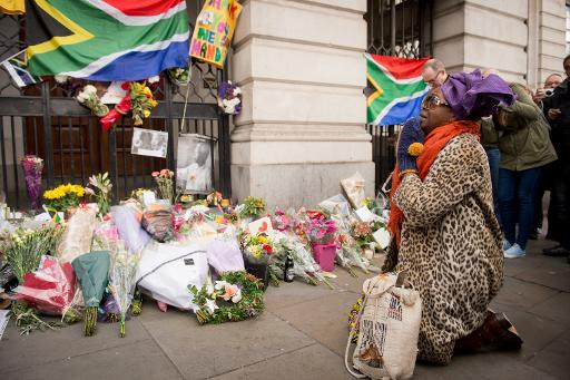 A woman kneels near to the floral tributes for Nelson Mandela at the South African High Commisson in Trafalgar Square, central London on December 6, 2013