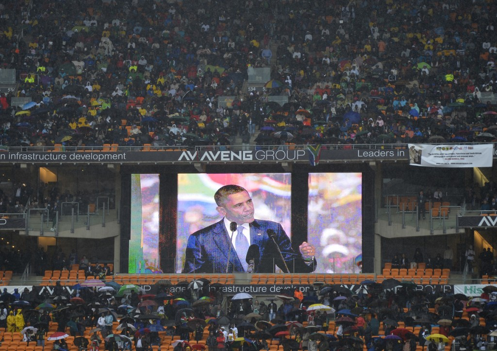 President Barack Obama is seen on a giant screen as he gives a speech during the memorial service of South African former president Nelson Mandela at the FNB Stadium (Soccer City) in Johannesburg on December 10, 2013.
