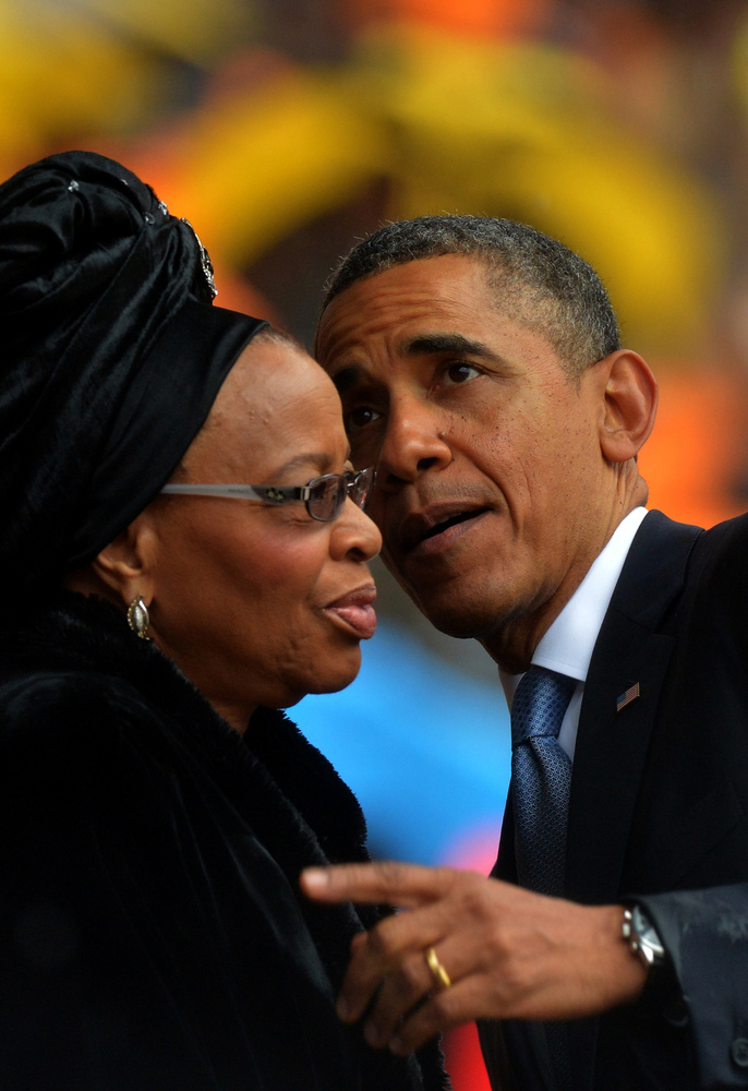 President Barack Obama (R) talks with the widow of South African President Nelson Mandela, Graca Machel, during the memorial service for Nelson Mandela at Soccer City Stadium in Johannesburg on December 10, 2013.