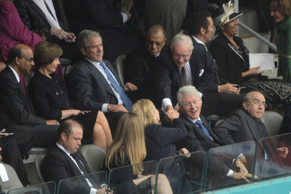Former US Secretary of State Hillary Clinton (bottom C), Former US President Bill Clinton (bottom 2R), Former US First Lady Laura Bush (top 2L) and Former US President George W. Bush attend the memorial service of South African former president Nelson Mandela at the FNB Stadium (Soccer City) in Johannesburg on December 10, 2013
