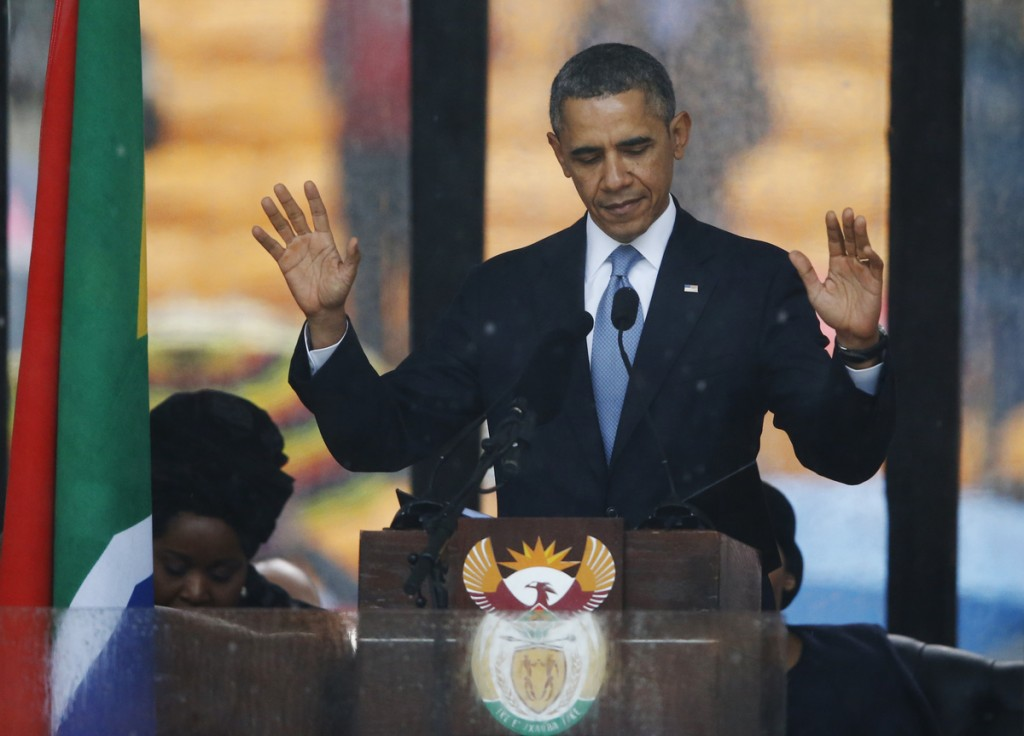 President Barrack Obama acknowledges applause before speaking at the memorial service for former South African president Nelson Mandela at the FNB Stadium in Soweto near Johannesburg, Tuesday, Dec. 10, 2013.