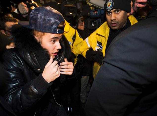 Justin Bieber is swarmed by media and police officers as he turns himself into Toronto police Wednesday for an expected assault charge