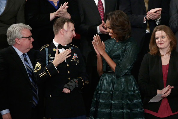 First lady Michelle Obama (R) stands with US Army Ranger Sergeant First Class Cory Remsburg before U.S. President Barack Obama delivers the State of the Union address to a joint session of Congress in the House Chamber at the U.S. Capitol on January 28, 2014 in Washington, DC.
