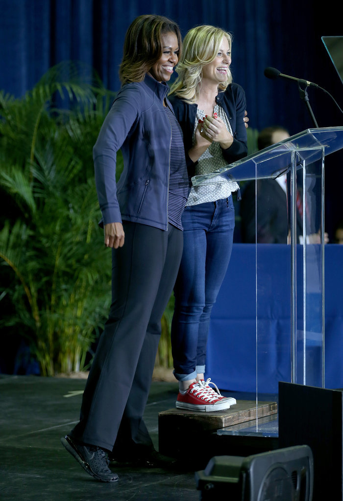 """Parks and Recreation's"" Amy Poehler and First Lady Michelle Obama celebrate the fourth anniversary of the first lady's ""Let's Move!"" initiative at the Gwen Cherry Park NFL/YET Center in Miami (Feb. 25, 2014)"