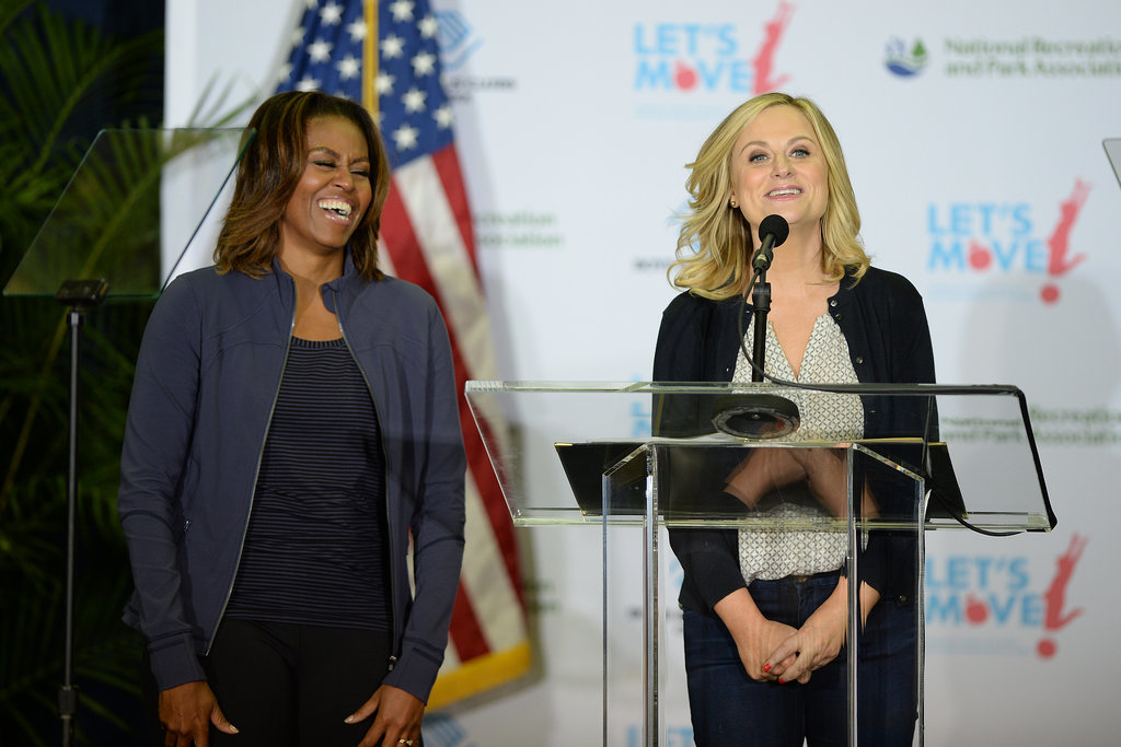 """Parks and Recreation's"" Amy Poehler and First Lady Michelle Obama celebrate the fourth anniversary of the first lady's ""Let's Move!"" initiative at the Gwen Cherry Park NFL/YET Center in Miami"
