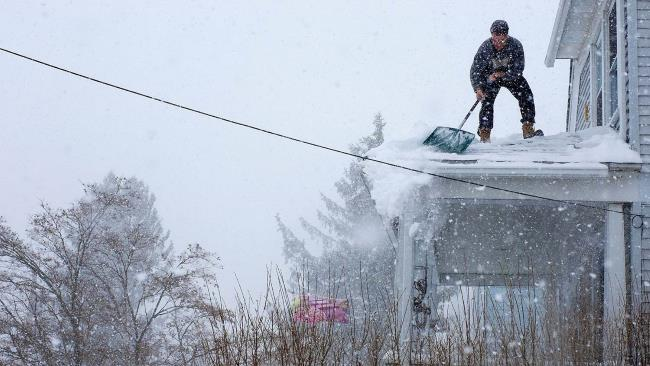 man on roof removing snow