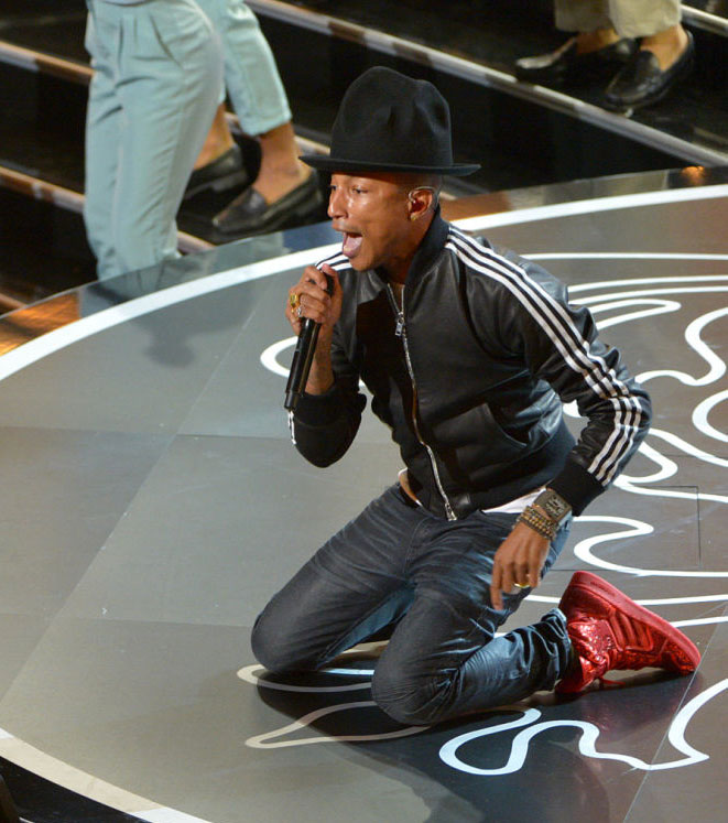 "Pharrell, in a leather adidas track jacket and custom red adidas sneakers, performs his Oscar nominated hit ""Happy"" at the 86th Academy Awards on March 2, 2014"