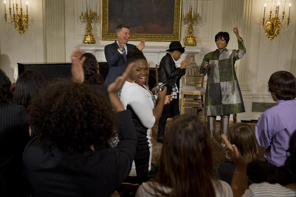 Robert Santelli, executive director of the GRAMMY Museum, left, applauds with singer Janelle Monáe, and Patti LaBelle, after an impromptu song by LaBelle, Thursday, March 6, 2014, in the State Dining Room of the White House in Washington