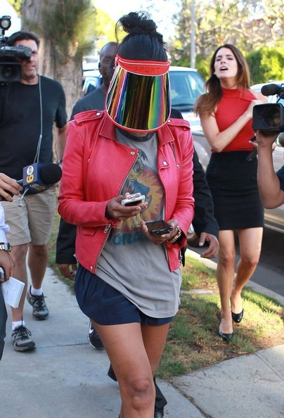 Donald Sterling's girlfriend V. Stiviano hides her face behind a mask as she stops by her house to change clothes and drop off groceries with her attorney in Los Angeles, California on April 28, 2014.