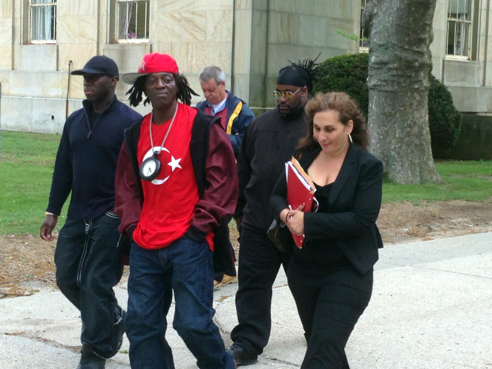 Flavor Flav, center, walks out of Nassau County Court in Mineola, N.Y. with his attorney, Indji Bessim, on Friday, May 16, 2014.