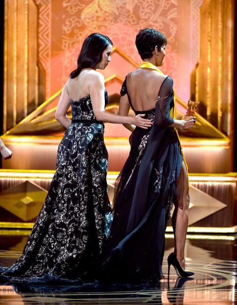 Actress Lucy Liu (L) walks actress Halle Berry offstage after presenting Berry with the Global Movie Icon Award at the 2014 Huading Film Awards at The Montalban Theatre on June 1, 2014 in Los Angeles
