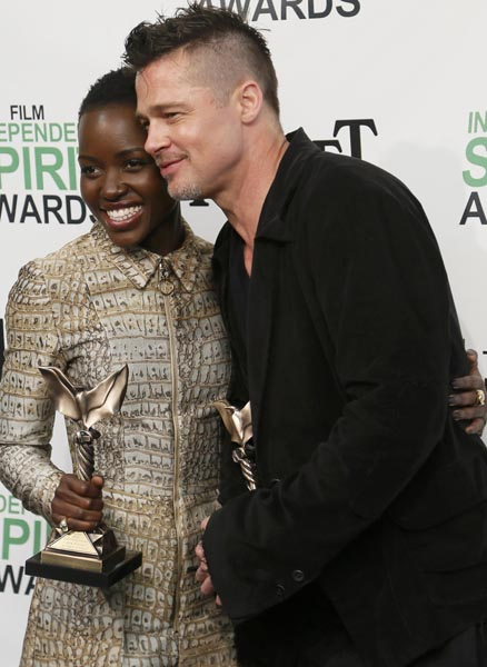 """Producer Brad Pitt and actress Lupita Nyong'o pose with their awards for """"12 Years a Slave""""  backstage at the 2014 Film Independent Spirit Awards in Santa Monica, California March 1, 2014."""