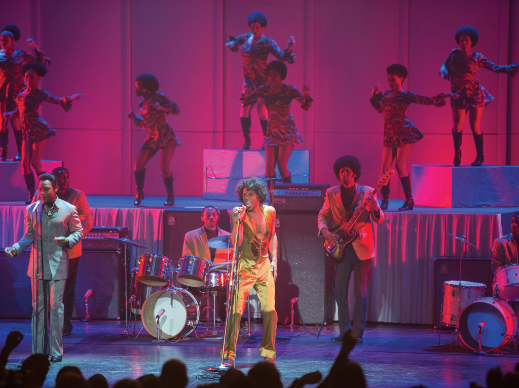 James Brown (Chadwick Boseman, center) in one of his stellar performances with wingman Bobby Byrd (Nelsan Ellis, Left), band and dancing girls