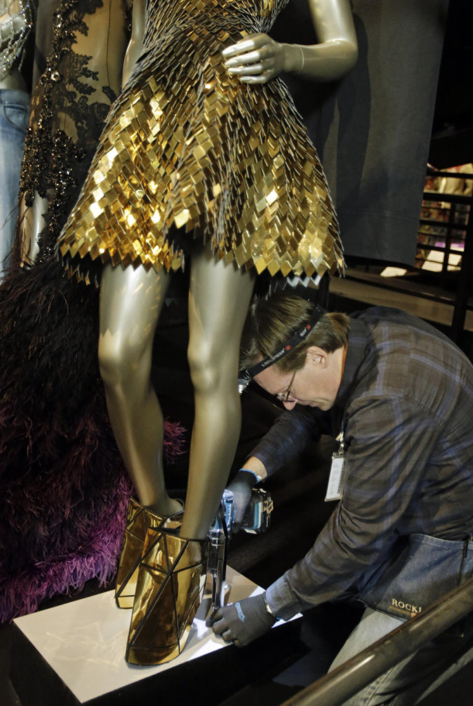 "In this Thursday, July 17, 2014 photo, Andre Sepetavec secures a mannequin with the outfit from Beyonce's ""Run the World (Girls)"" in a new exhibit at the Rock and Roll Hall of Fame in Cleveland."