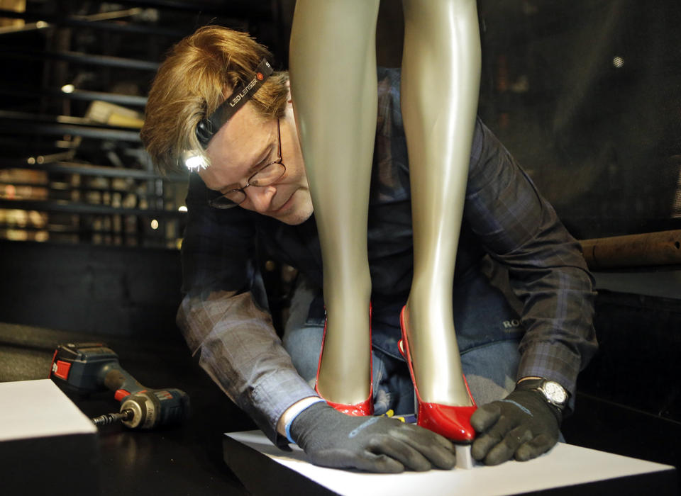 "In this Thursday, July 17, 2014 photo, Andre Sepetavec adjusts the shoes for Beyonce's ""Crazy in Love"" outfit during installation of the new exhibit at the Rock and Roll Hall of Fame in Cleveland."