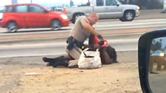 Screen shot taken from cellphone video shows CHP officer pummeling woman by side of road.