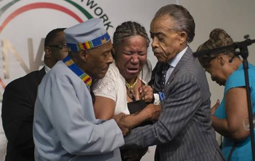 Esaw Garner (wife of Eric) bursts to tears as Revs. Herbert Daughtry (left) and Al Sharpton (right) console her.