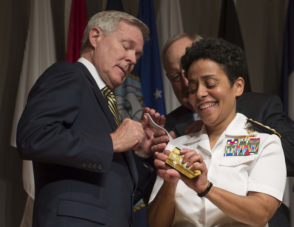 U.S. Navy, Adm. Michelle Howard lends a hand to Secretary of the Navy (SECNAV) Ray Mabus as he and Wayne Cowles, Howard's husband, put four-star shoulder boards on Howard's service white uniform during her promotion ceremony at the Women in Military Service for America Memorial on July 1, 2014 in Washington, D.C.