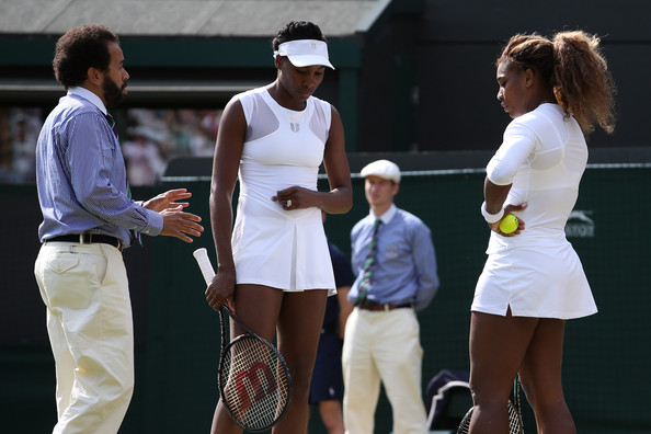 Chair umpire Kader Nouni talks with Serena and Venus Williams of the United States before the are forced through illness to quit their Ladies Doubles second round match with against Kristina Barrois of Germany and Stefanie Voegele of Switzerland on day eight of the Wimbledon Lawn Tennis Championships at the All England Lawn Tennis and Croquet Club on July 1, 2014 in London, England