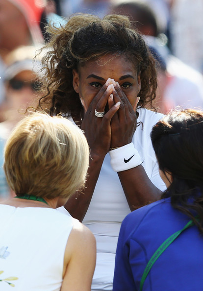 Serena Williams of the United States recieves treatment during the warm up before their Ladies Doubles second round match with Venus Williams against Kristina Barrois of Germany and Stefanie Voegele of Switzerland on day eight of the Wimbledon Lawn Tennis Championships at the All England Lawn Tennis and Croquet Club on July 1, 2014 in London, England